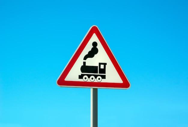 Railroad level crossing sign ohne barriere oder tor vor der straße, hüten sie sich vor dem straßenschild der dampflokomotive am straßenrand am wegweiser. zugschild eisenbahn voraus.