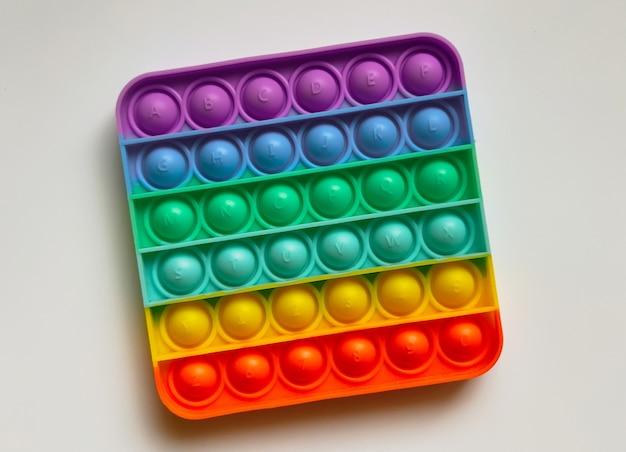 Rainbow anti-stress-finger-push-spielzeug für kinder knallen es isoliert auf weißem hintergrund.