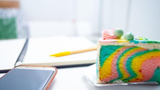 Rainbow cake-creme und buch, stift, mobile werden auf einen weißen hintergrund gelegt.
