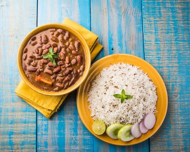 Rajma oder razma ist ein beliebtes nordindisches essen, das aus gekochten roten kidneybohnen in einer dicken soße mit gewürzen besteht. serviert in einer schüssel mit jeera reis und grünem salat Premium Fotos