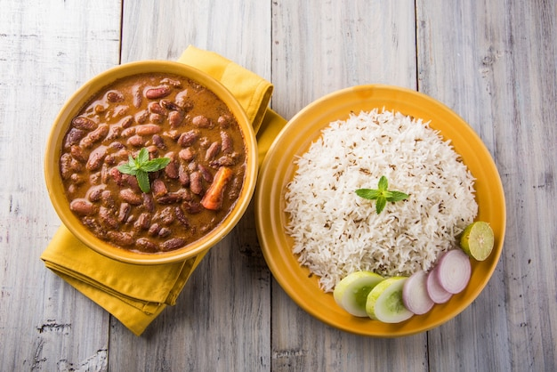 Rajma oder razma ist ein beliebtes nordindisches essen, das aus gekochten roten kidneybohnen in einer dicken soße mit gewürzen besteht. serviert in einer schüssel mit jeera reis und grünem salat
