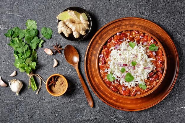 Rajma red bean masala, red bean kidney curry, mit reis in einer tonschüssel auf einem betontisch mit zutaten, horizontale ansicht von oben, flach