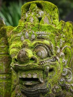 Rakasa balinesische steinskulptur bedeckt mit moos.