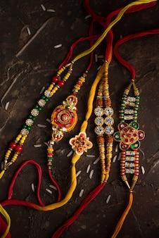 Raksha bandhan feier mit einem eleganten rakhi und verstreutem reis. ein traditionelles indisches armband, das ein symbol der liebe zwischen brüdern und schwestern ist.