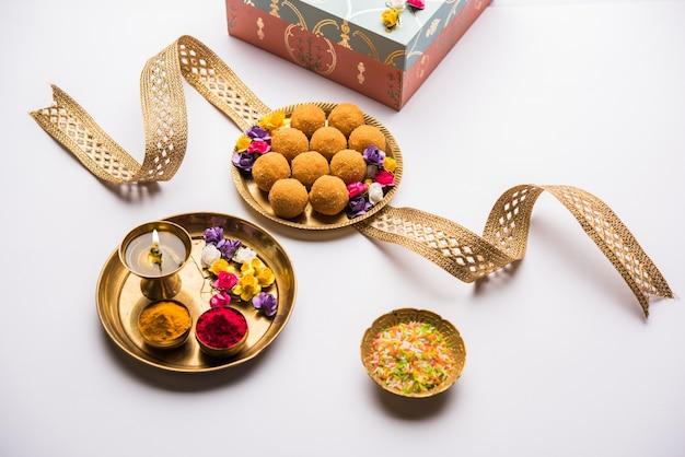 Raksha-bandhan-festival: konzeptionelles rakhi, das mit einem teller voller bundi laddu-süßigkeiten mit band und pooja thali hergestellt wird. ein traditionelles indisches armband - symbol der liebe zwischen bruder und schwester