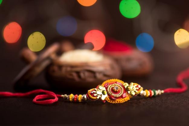 Raksha bandhan mit einem eleganten rakhi, reiskörnern und kumkum. ein traditionelles indisches armband, das ein symbol der liebe zwischen brüdern und schwestern ist.