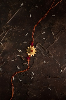 Raksha bandhan mit einem eleganten rakhi und verstreutem reis. ein traditionelles indisches armband, das ein symbol der liebe zwischen brüdern und schwestern ist.