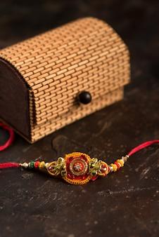 Raksha bandhan mit elegantem rakhi, reiskörnern, kumkum und geschenkbox. ein traditionelles indisches armband, das ein symbol der liebe zwischen brüdern und schwestern ist.