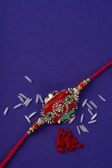Raksha bandhan: rakhi mit reiskörnern und kumkum. ein indisches fest. traditionelles indisches armband, das ein symbol der liebe zwischen brüdern und schwestern ist.