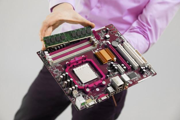Ram und motherboard in der handnahaufnahme der männer auf licht