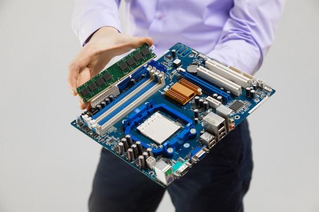 Ram und motherboard in der handnahaufnahme der männer lokalisiert auf licht
