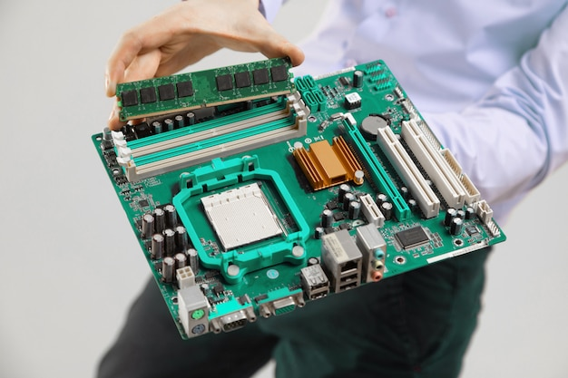 Ram und motherboard in der handnahaufnahme der männer lokalisierten licht