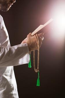Ramadam-ereignis und arabischer mann, die koran und gebetsperlen halten