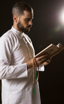 Ramadam-ereignis und arabischer mann, die mit koran und gebetsperlen stehen