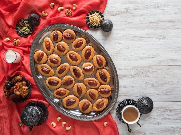 Ramadan essen tisch. eid dates süßigkeiten auf einem weißen holztisch, draufsicht.