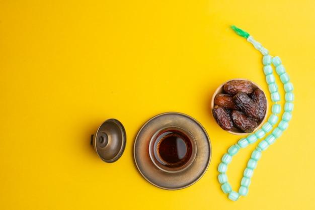 Ramadan kareem festival, daten auf hölzerner schüssel mit schale schwarzem tee und rosenbeet auf gelbem hintergrund