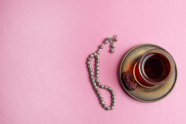 Ramadan kareem festival, rosenbeet und cup schwarzer tee auf rosa hintergrund.