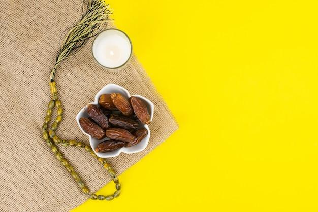 Ramadan kareem festival. schließen sie oben von getrockneten dattelfrüchten in der schüssel mit kerze und rosenkranz auf gelbem hintergrund. speicherplatz kopieren