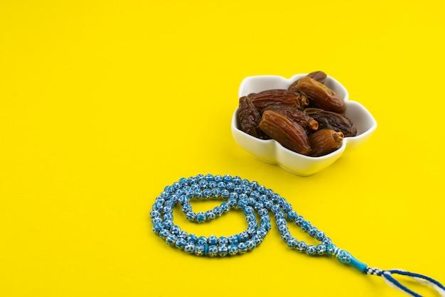 Ramadan kareem festival. schließen sie oben von getrockneten datteln frucht in schüssel mit rosenkranz auf gelbem hintergrund. speicherplatz kopieren.