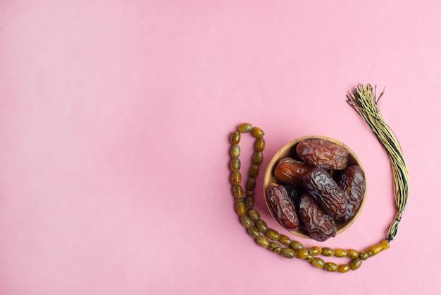 Ramadan kareem festival, termine an der schüssel mit rosenbeet auf rosa hintergrund