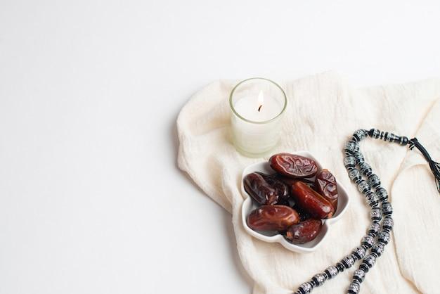 Ramadan kareem festival, termine bei schüssel mit rosenkranz und weißer kerze