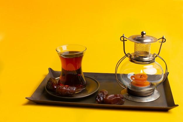 Ramadan kareem festive, close up of datums auf platte mit orientalischer kerzenlampe und tasse schwarzen tee