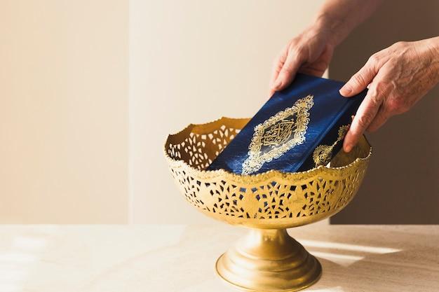 Ramadan-konzept mit den händen, die quran in schüssel setzen