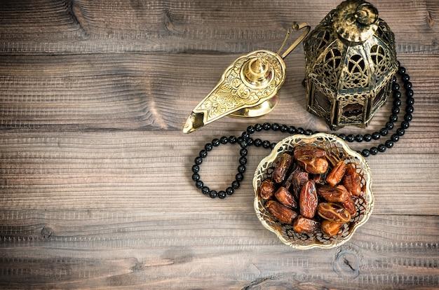 Ramadan-lampe, rosenkranz und datteln auf holzhintergrund. festliches stillleben mit orientalischer laterne. getöntes bild im vintage-stil mit vignette