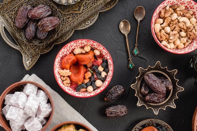 Ramadan saftige datteln und getrocknete früchte; nüsse und lukum auf schwarzem hintergrund