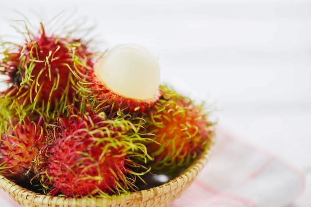 Rambutan geschält in einem korb auf tabellenhintergrund frische rambutansommerfrucht vom garten