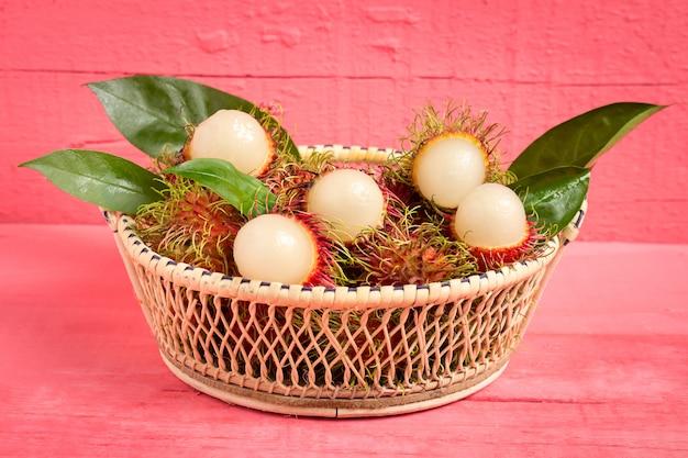 Rambutanfrucht auf hölzernem farbrosa. im korb