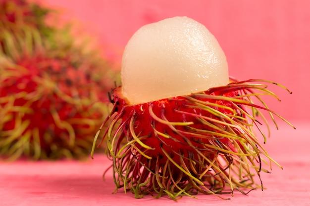 Rambutanfrucht auf hölzernem farbrosa