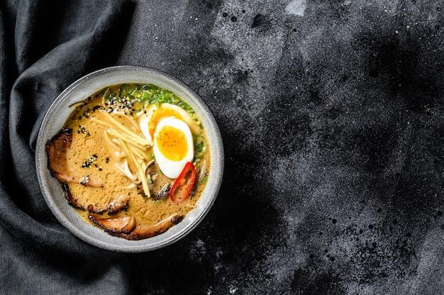 Ramen asiatische nudelsuppe mit rinderzungenfleisch, pilzen und eingelegtem ajitama-ei. schwarzer hintergrund. draufsicht. speicherplatz kopieren