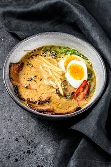 Ramen asiatische nudelsuppe mit rinderzungenfleisch, pilzen und eingelegtem ajitama-ei. schwarzer hintergrund. draufsicht