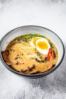 Ramen asiatische nudelsuppe mit rinderzungenfleisch, pilzen und eingelegtem ajitama-ei. weißer hintergrund. draufsicht
