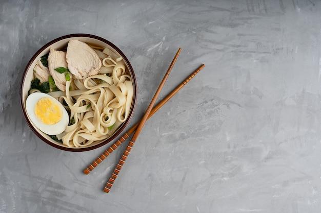 Ramen-suppe mit hühnerfleisch und halbiertem ei in der schüssel auf betontisch mit stäbchen