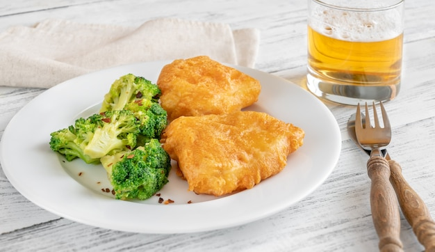 Ramponierter fisch mit gedämpftem brokkoli und einem glas bier