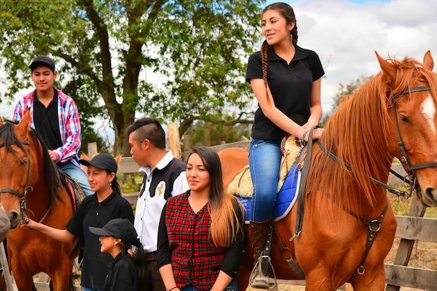 Rancho fenix, latacunga, cotopaxi, ecuador 12. august 2016. verschiedene leute, die neben 2 pferden mit zwei reitern stehen