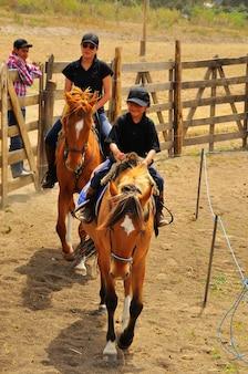 Rancho fenix, latacunga, cotopaxi, ecuador 12. august 2016. zwei lächelnde mädchen auf pferden
