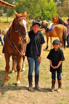 Rancho fenix, latacunga, cotopaxi, ecuador 12. august 2016. zwei lächelnde mädchen neben einem pferd