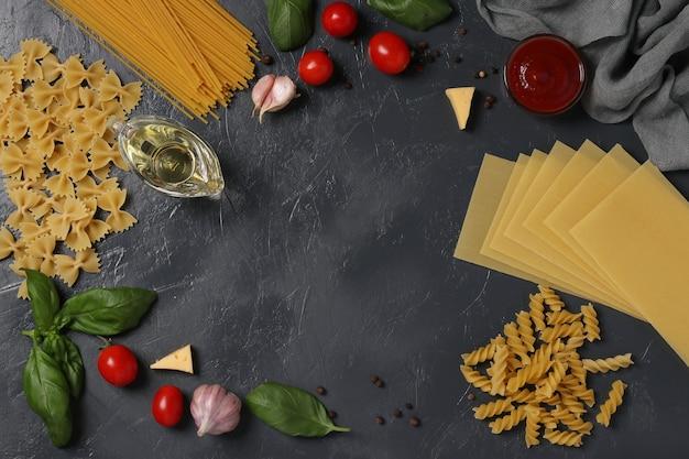 Rand von rohem nudel-hartweizen, tomatensauce, kirschtomaten, basilikum und gewürzen auf dunkelgrau. sicht von oben. flatlay-stil.