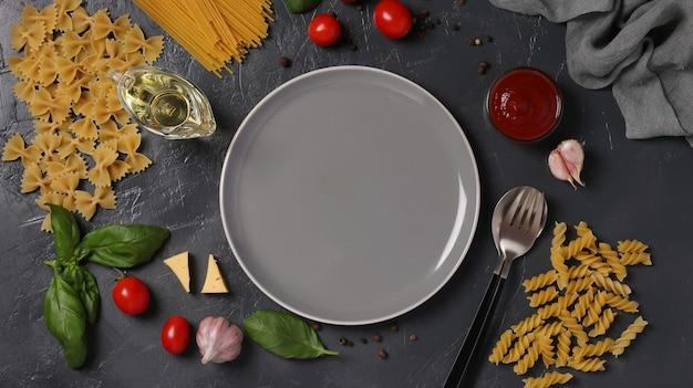Rand von rohem nudel-hartweizen, tomatensauce, kirschtomaten, basilikum und knoblauch auf dunkelgrau. sicht von oben. flatlay-stil.
