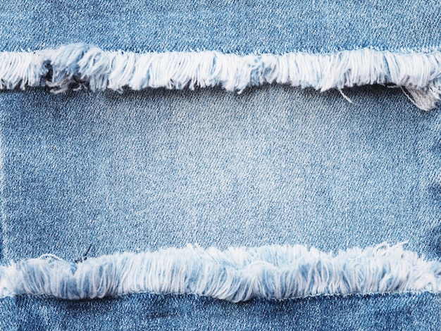 Randrahmen des blauen denims über jeansbeschaffenheitshintergrund gerissen.