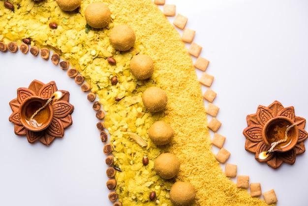 Rangoli oder design aus indischen snacks und süßigkeiten und diya oder lampe für die diwali-festivalfeier