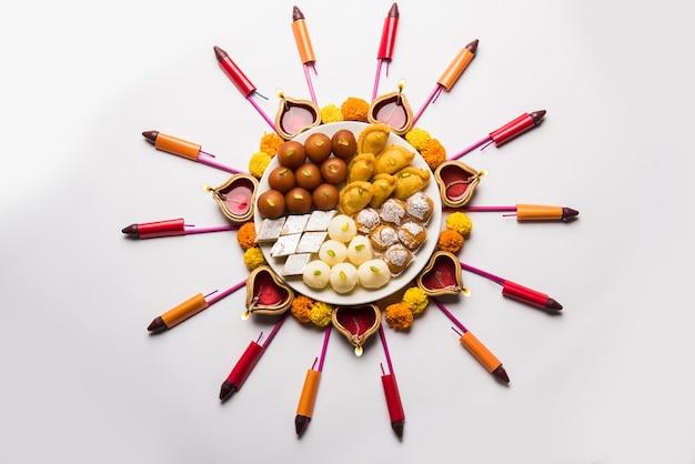 Rangoli oder design mit diya oder öllampe, blumen und süßigkeiten wie gulab jamun, rasgulla, kaju katli, morichoor oder bundi laddu, gujiya oder karanji für diwali-feiern