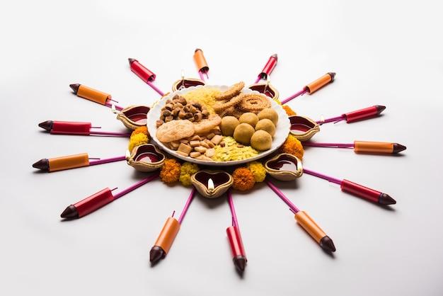 Rangoli oder design mit diya oder öllampe mit indischen snacks oder süßigkeiten und feuerwerkskörpern oder patakhe für das diwali-festival