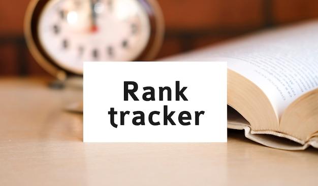 Rank-tracker-text auf einem weißen buch und einer uhr