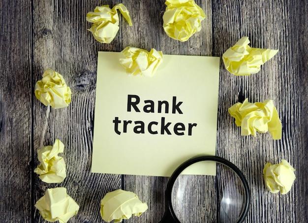 Rank-tracker-text auf gelben notizblättern auf einer dunklen holzoberfläche mit zerknitterten blättern und einer lupe