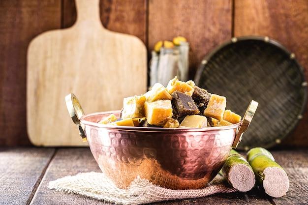Rapadura-bonbons in stücken in einem kupfertopf, bonbons aus zuckerrohr oder melasse aus zuckerrohr