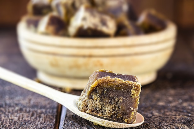 Rapadura-bonbons in stücken in holzlöffel, bonbons aus zuckerrohrmelasse